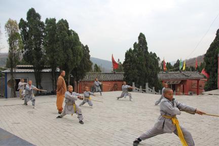 少林寺承办的少林武校教练教学生练习少林棍法