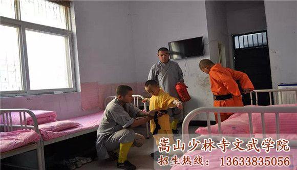 嵩山少林寺武术学校的教练在帮助孩子穿衣服