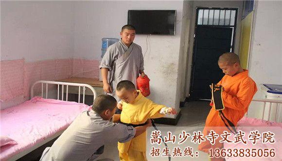 嵩山少林寺武校的教练在帮小学员穿衣服